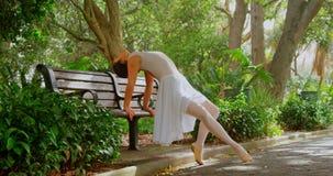 Όμορφο νέο ballerina που κάνει την τεντώνοντας άσκηση στον πάγκο στο πάρκο 4k απόθεμα βίντεο