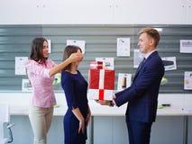 Όμορφο νέο brunette και όμορφο άτομο με ένα μεγάλο δώρο για το συνάδελφο χρυσή ιδιοκτησία βασικών πλήκτρων επιχειρησιακής έννοιας στοκ εικόνες