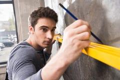 Όμορφο νέο laborer με το μολύβι που μετρά τον τοίχο με το εργαλείο επιπέδων Στοκ φωτογραφίες με δικαίωμα ελεύθερης χρήσης