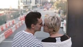 Όμορφο νέο multiethnic ρομαντικό ζεύγος που στέκεται σε μια γέφυρα που απολαμβάνει την καλή θέα οδών της Νέας Υόρκης και που φιλά απόθεμα βίντεο