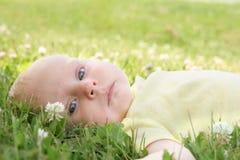 Όμορφο νεογέννητο κοριτσάκι που βάζει στη χλόη έξω Στοκ φωτογραφία με δικαίωμα ελεύθερης χρήσης