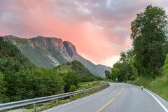 Όμορφο νορβηγικό πανόραμα - δρόμος βουνών, που οδηγεί σε ένα ρόδινο ηλιοβασίλεμα Στοκ Εικόνες