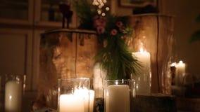 Όμορφο ντεκόρ τελετής δέσμευσης χειμερινού γάμου Χριστουγέννων με τα κεριά, τα κούτσουρα σημύδων, τις γιρλάντες βολβών και το δέν απόθεμα βίντεο