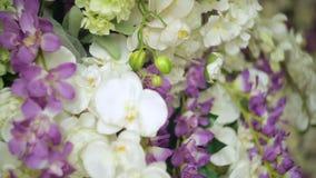 Όμορφο ντεκόρ των λουλουδιών για την κινηματογράφηση σε πρώτο πλάνο γαμήλιας τελετής φιλμ μικρού μήκους