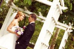 Όμορφο νυφικό ζεύγος που έχει τη διασκέδαση στο πάρκο στην ανθοδέσμη λουλουδιών ημέρας γάμου τους Στοκ φωτογραφίες με δικαίωμα ελεύθερης χρήσης