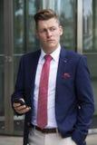 Όμορφο ξανθό άτομο στο κοστούμι που στέκεται έξω με το τηλέφωνό του Στοκ φωτογραφία με δικαίωμα ελεύθερης χρήσης