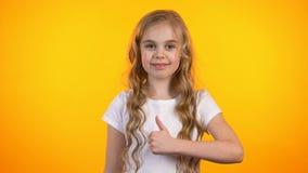 Όμορφο ξανθό έφηβη που κάνει αντίχειρας-επάνω στη σύσταση χειρονομίας και κλεισίματος του ματιού απόθεμα βίντεο