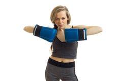 Όμορφο ξανθό αθλητικό κορίτσι στα ομοιόμορφα και μπλε εγκιβωτίζοντας γάντια που εξετάζει τη κάμερα Στοκ εικόνα με δικαίωμα ελεύθερης χρήσης