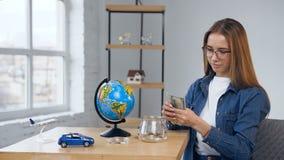 Όμορφο ξανθό βάζο γυαλιού ανοίγματος γυναικών με τα χρήματα απόθεμα βίντεο