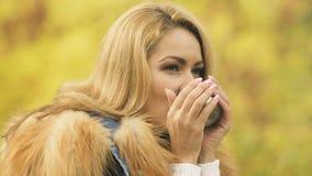Όμορφο ξανθό καυτό τσάι κατανάλωσης υπαίθριο, απολαμβάνοντας το φθινόπωρο, την άνεση και τη ζεστασιά απόθεμα βίντεο