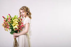 Όμορφο ξανθό κορίτσι άνοιξη με τα μεγάλα λουλούδια ανθοδεσμών Στοκ Φωτογραφίες