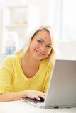 Όμορφο ξανθό κορίτσι με ένα σημειωματάριο στο σπίτι Στοκ Εικόνα