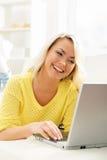 Όμορφο ξανθό κορίτσι με ένα PC σημειωματάριων στο σπίτι Στοκ Φωτογραφία