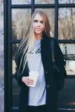 Όμορφο ξανθό κορίτσι με μακρυμάλλη σε μια μοντέρνη μαύρη εξάρτηση που βγαίνει από έναν καφέ με ένα φλιτζάνι του καφέ εγγράφου Στοκ Εικόνες