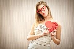 Όμορφο ξανθό κορίτσι με τα γυαλιά καρδιών με το δώρο αγάπης κιβωτίων σοκολάτας Στοκ Εικόνα