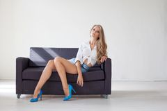 Όμορφο ξανθό κορίτσι με τα μπλε μάτια που κάθεται στον καναπέ σε ένα άσπρο δωμάτιο 1 Στοκ Εικόνες