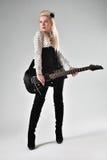 Όμορφο ξανθό κορίτσι με τη μαύρη ηλεκτρική κιθάρα Στοκ Φωτογραφίες