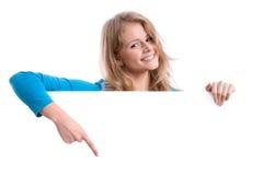 Όμορφο ξανθό κορίτσι πίσω από έναν κενό λευκό πίνακα Στοκ φωτογραφία με δικαίωμα ελεύθερης χρήσης
