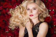 Όμορφο ξανθό κορίτσι που βρίσκεται στο υπόβαθρο των τριαντάφυλλων Μπούκλες, κόκκινο κραγιόν, που εξισώνουν το φόρεμα Πρόσωπο ομορ Στοκ Φωτογραφία