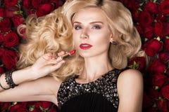 Όμορφο ξανθό κορίτσι που βρίσκεται στο υπόβαθρο των τριαντάφυλλων Μπούκλες, κόκκινο κραγιόν, που εξισώνουν το φόρεμα Πρόσωπο ομορ Στοκ εικόνες με δικαίωμα ελεύθερης χρήσης