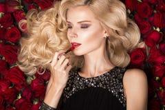Όμορφο ξανθό κορίτσι που βρίσκεται στο υπόβαθρο των τριαντάφυλλων Μπούκλες, κόκκινο κραγιόν, που εξισώνουν το φόρεμα Πρόσωπο ομορ Στοκ Εικόνες