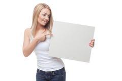 Όμορφο ξανθό κορίτσι που κρατά την κενή αφίσα στοκ φωτογραφία με δικαίωμα ελεύθερης χρήσης