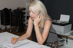 Όμορφο ξανθό κορίτσι που παίρνει ένα τηλεφώνημα στο κατάστημα ενός κομμωτή Στοκ εικόνες με δικαίωμα ελεύθερης χρήσης
