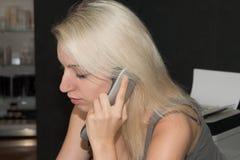 Όμορφο ξανθό κορίτσι που παίρνει ένα τηλεφώνημα Στοκ Φωτογραφίες