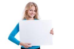 Όμορφο ξανθό κορίτσι που παρουσιάζει κενό λευκό πίνακα Στοκ εικόνα με δικαίωμα ελεύθερης χρήσης