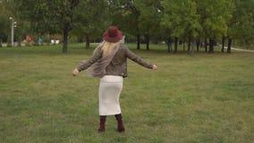 Όμορφο ξανθό κορίτσι που περπατά στο πάρκο φιλμ μικρού μήκους