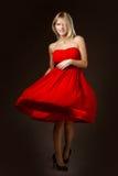 Όμορφο ξανθό κορίτσι σε ένα κόκκινο φόρεμα Στοκ Φωτογραφίες