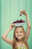 Όμορφο ξανθό κορίτσι σε ένα υπόβαθρο του τυρκουάζ πιάτου εκμετάλλευσης τοίχων με τα κεράσια το κεφάλι της Στοκ Εικόνες