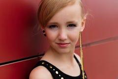 Όμορφο ξανθό κορίτσι σε μια μαύρη τοποθέτηση φορεμάτων ενάντια σε έναν κόκκινο τοίχο Στοκ φωτογραφία με δικαίωμα ελεύθερης χρήσης