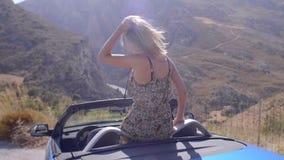 Όμορφο ξανθό κορίτσι σε μπλε Cabrio φιλμ μικρού μήκους