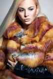 Όμορφο ξανθό κορίτσι στη ζωηρόχρωμη γούνα στοκ εικόνα με δικαίωμα ελεύθερης χρήσης