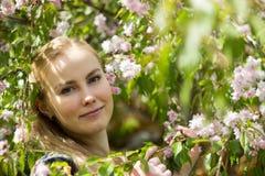 Όμορφο ξανθό κορίτσι στον κήπο ανθών Στοκ Εικόνες