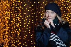 Όμορφο ξανθό κορίτσι στο θολωμένο υπόβαθρο των κίτρινων φω'των Στοκ Εικόνες