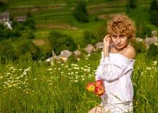 Όμορφο ξανθό κορίτσι στο λευκό με τα κόκκινα μήλα ενάντια στο μπλε ουρανό στον πράσινο τομέα στοκ εικόνες