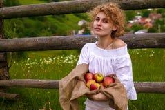 Όμορφο ξανθό κορίτσι στο λευκό με τα κόκκινα μήλα ενάντια στο μπλε ουρανό στον πράσινο τομέα στοκ φωτογραφία με δικαίωμα ελεύθερης χρήσης