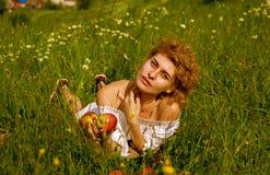 Όμορφο ξανθό κορίτσι στο λευκό με τα κόκκινα μήλα ενάντια στο μπλε ουρανό στον πράσινο τομέα στοκ φωτογραφίες με δικαίωμα ελεύθερης χρήσης