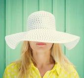Όμορφο ξανθό κρύψιμο κοριτσιών πίσω από τους τομείς καπέλων Στοκ φωτογραφία με δικαίωμα ελεύθερης χρήσης