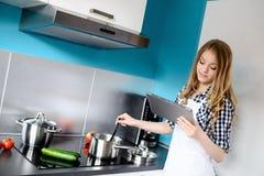 Όμορφο ξανθό μαγειρεύοντας γεύμα γυναικών στην κουζίνα Στοκ φωτογραφίες με δικαίωμα ελεύθερης χρήσης