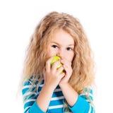 Όμορφο ξανθό μικρό κορίτσι που τρώει το πράσινο μήλο Στοκ Φωτογραφίες