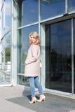 Όμορφο ξανθό νέο κορίτσι σε ένα όμορφο μπεζ παλτό, τζιν και υψηλά τακούνια Στοκ Φωτογραφίες