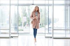 Όμορφο ξανθό νέο κορίτσι σε ένα όμορφο μπεζ παλτό, τζιν και υψηλά τακούνια Στοκ εικόνα με δικαίωμα ελεύθερης χρήσης