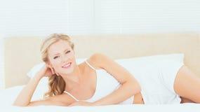 Όμορφο ξανθό να βρεθεί στο κρεβάτι της που χαμογελά στη κάμερα Στοκ Φωτογραφία