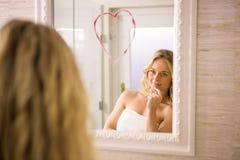 Όμορφο ξανθό να φανεί μια μεγάλη καρδιά στον καθρέφτη Στοκ Εικόνες