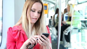 Όμορφο ξανθό οδηγώντας τραμ γυναικών, που δακτυλογραφεί σε κινητό, τηλέφωνο, κύτταρο, χείλια δαγκώματος απόθεμα βίντεο