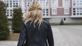 Όμορφο ξανθό περπάτημα στο πεζοδρόμιο γύρω από το μοντέρνο σπίτι Είναι νεολαία απόθεμα βίντεο