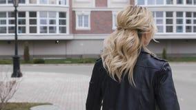 Όμορφο ξανθό περπάτημα στο πεζοδρόμιο γύρω από το μοντέρνο σπίτι Είναι νεολαία φιλμ μικρού μήκους